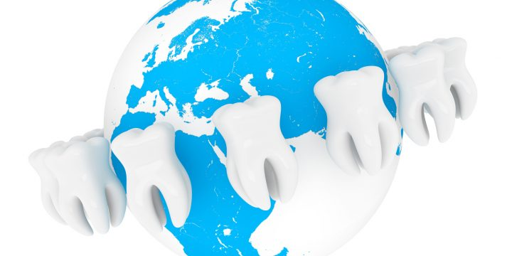 World Stomatology concept. Extreme closeup tooth with globe on a white background