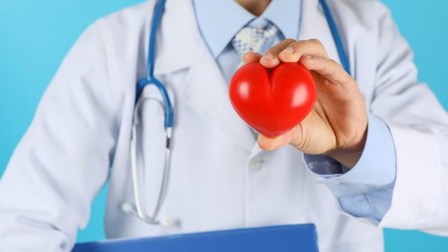 Doctor with stethoscope and heart against blue background, close