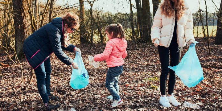 Family cleaning up a forest. Volunteers picking plastic waste to bags. Concept of plastic pollution and too many plastic waste. Environmental issue. Environmental damage. Responsibilitiy for environment. Real people, authentic situations
