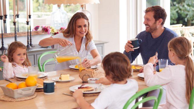 Family Wearing Pyjamas Sitting Around Table Enjoying Pancake Breakfast Together