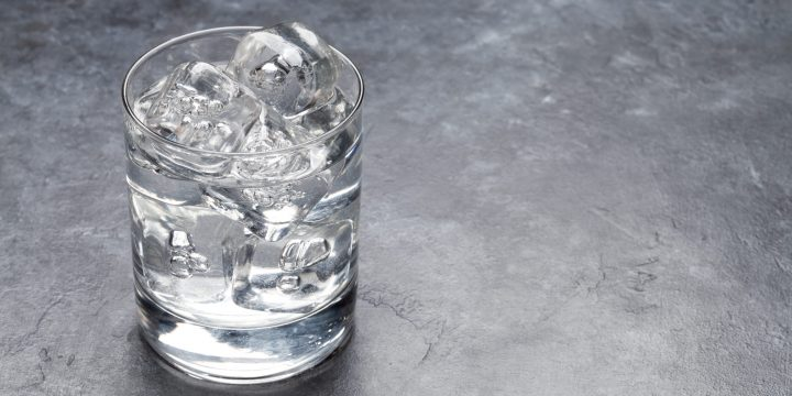 Glass of water with ice cubes on stone table. With copy space