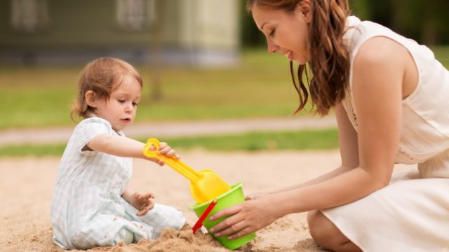 family, childhood and parenthood concept - happy mother and little baby girl with sand toys playing in sandbox at summer playground