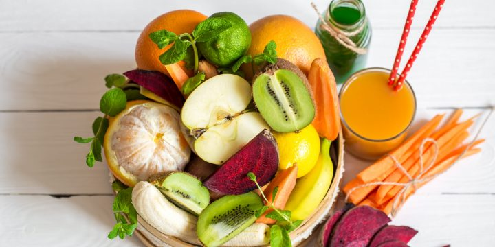 A variety of fresh fruits with juice on white wooden background,concept of healthy nutrition and food