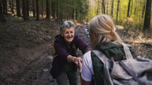 Senior women hikers outdoors walking in forest in nature, helping each other.